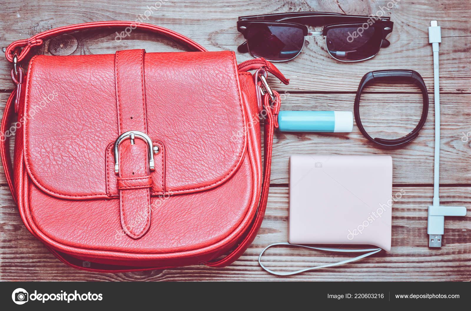 Sac cuir rouge autres accessoires féminins disposition sur bureau