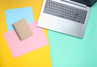 Laptop, notebook on a colored pastel background, modern workspace, minimalism, flat lay style, top vie