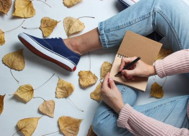 A girl in jeans and sneakers sits on  white background among the fallen yellow leaves and writes in a notebook. Work journalist. Autumn time. Working space