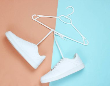 Flat Lay of Modern White Sneakers  Shoes With Hanger On Pastel Background. Overhead Top View Photography. Youth Lifestyle Concept