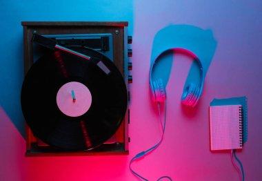 Vinyl player with lp record, headphones. Nightclub. Retro wave, red blue neon light, ultraviolet. Top view, minimalism