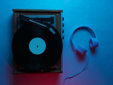 Vinyl player with lp record. Retro wave, neon light, ultraviolet. Nightclub. Top view, minimalism