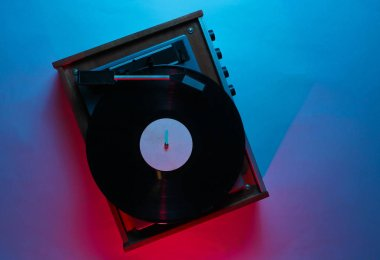 Vinyl player with lp record. Retro wave, red blue neon light, ultraviolet. Top view, minimalism