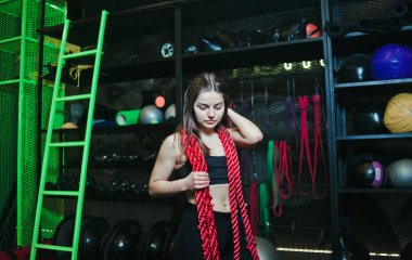 Muscular young woman in sportswear with a rope around her neck posing at modern gym for functional training
