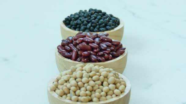 Sortiment Bohnen in kleinen Holzschalen: rote Bohnen, Sojabohnen, Mungbohnen
