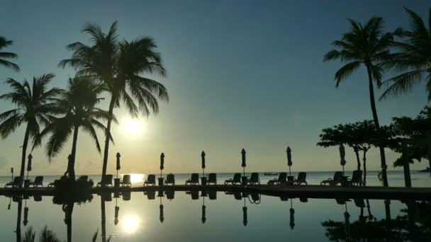 Západ slunce na bazén, slunečníky a bujné tropické vegetace
