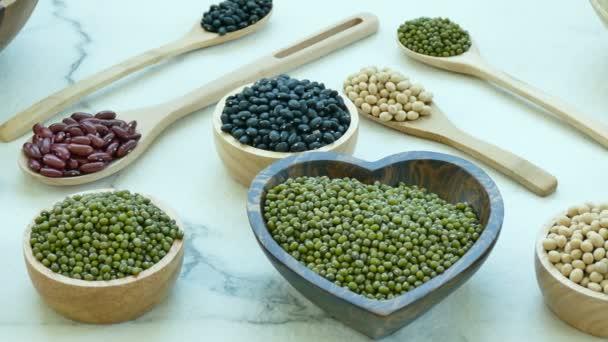 Auswahl der Bohnen in kleine hölzerne Schüsseln und Löffel: rote und schwarze Bohnen, Sojabohnen, Mungobohnen