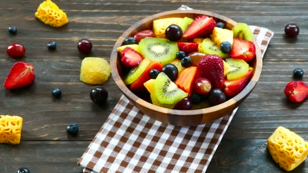 assorted ripe fruits and berries in wooden bowl on rustic table