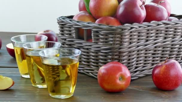 pile of fresh apples in wooden box and glasses of juice