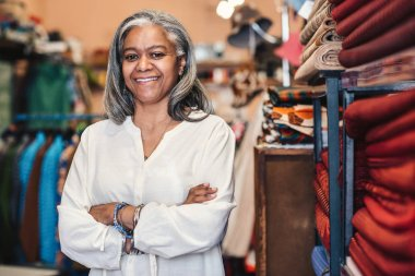 Smiling mature fabric shop owner standing in her store with her arms crossed surrounded by colorful cloths and textiles