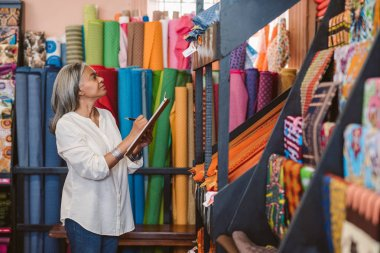 Mature fabric store owner standing in her shop surrounded by colorful cloths and textiles taking inventory with a clipboard