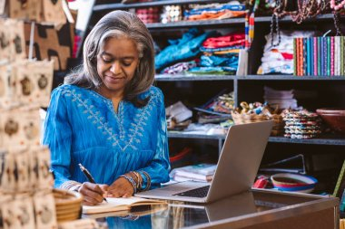 Smiling mature fabric shop owner writing in a notebook and working on a laptop at a counter surrounded by colorful cloths and textiles