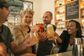 Fotografie Vielfältige Gruppe junger Freunde, die gemeinsam in einer trendigen Bar lachen und gemeinsam mit Getränken jubeln