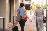 Photo Rearview of a young lesbian couple walking hand in hand down a street in the city carrying shopping bags while enjoying a day out together