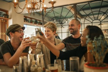 Diverse group of young friends laughing and toasting with drinks while hanging out together in a trendy bar