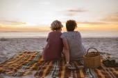 Zpětná obsahu mladé lesby na dece na pláži sledovat romantický západ slunce
