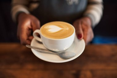 Closeup of an African barista standing behind the counter of a cafe offering up a fresh cup of cappuccino