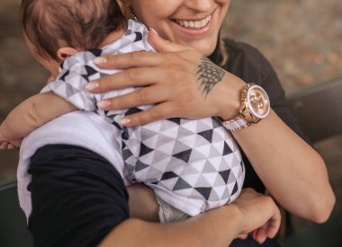 Closeup of a smiling young mother sitting outside on a bark bench cradling her adorable baby boy over her shoulder