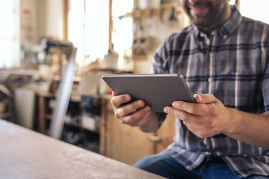 Closeup of a smiling woodworker sitting at a table in his large carpentry workshop working online with a digital tablet