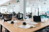 Interiér moderního kancelářského zasedací místnosti obsahující stůl a židle, notebook a kancelářské potřeby po schůzce