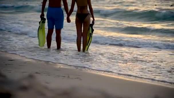 Silhouette pár szerelmes nászút nyaralni a trópusi nyári strand a naplementében élénk ég. Kültéri utazás életmód koncepció. tengeri strand hullám a tengerparton a nyári időszakban táj