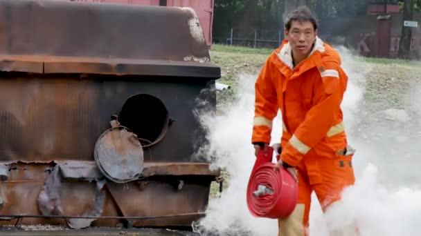 Hasič bojující s protipožární ochranou. Hasič nosí pevnou čepici, uniformu v ochranném obleku pro ochranu před požárem. Záchrana vyškolená v hasicím přístroji nebezpečné požáry