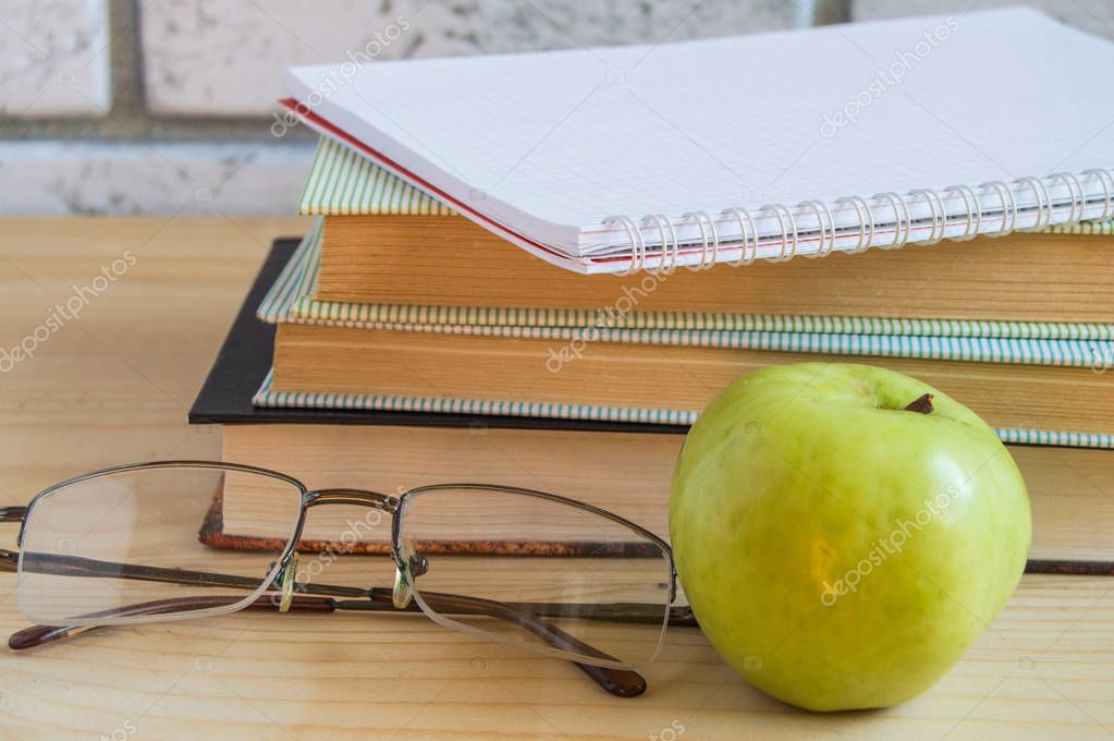 book, Apple, notebook, reading glasses and pen on wooden table. Back to school concept.
