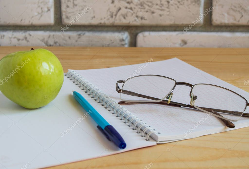 Apple, notebook, reading glasses and pen on wooden table. Back to school concept.