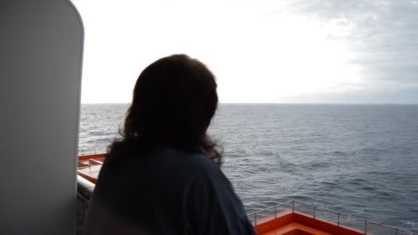 A woman stands with her back on the deck of a cruise ship and looks at the sea in the evening after sunset