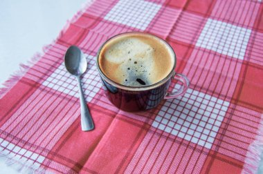 Glass Cup of espresso on a red checkered napkin, morning coffee.
