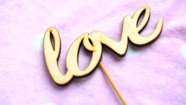 Slovo láska vyrobené z dřevěných písmen na delikátní růžové pozadí