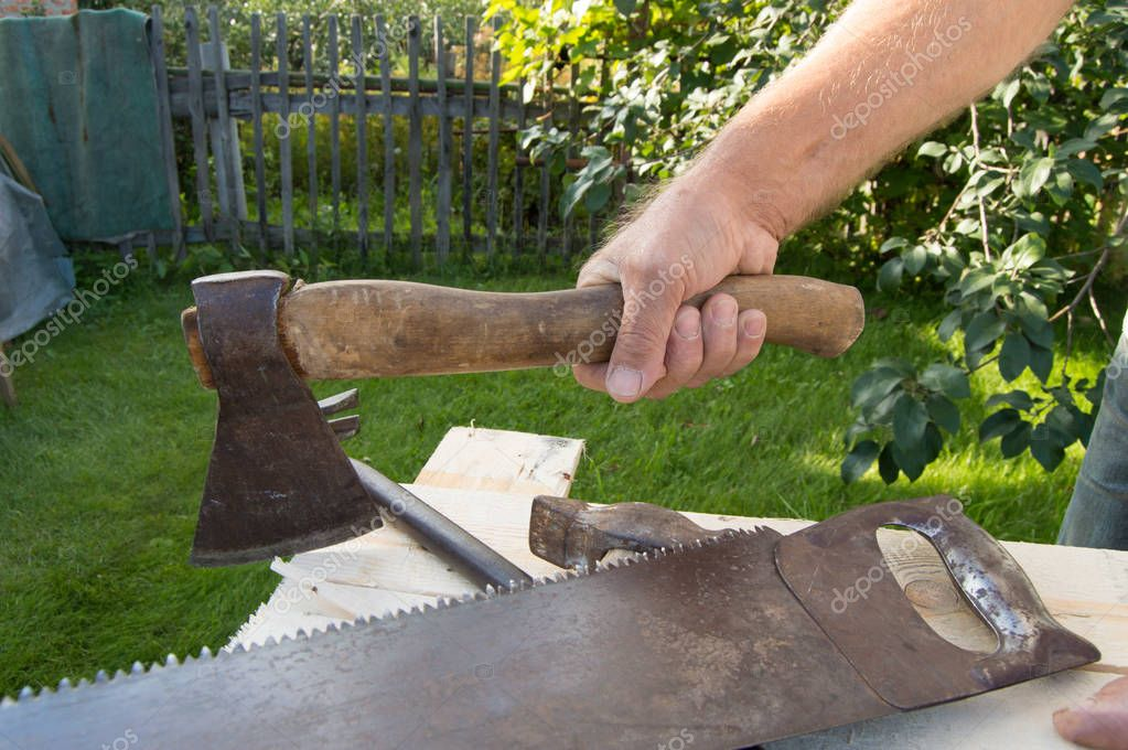man holding the axe, working with construction tools in his garden