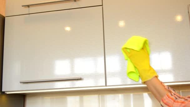 Die Hand einer Frau in einem gelben Gummihandschuh reinigt mit einem Tuch die glänzende Oberfläche eines modernen Küchenschranks aus Kunststoff. Frühjahrsputz und Hausarbeit