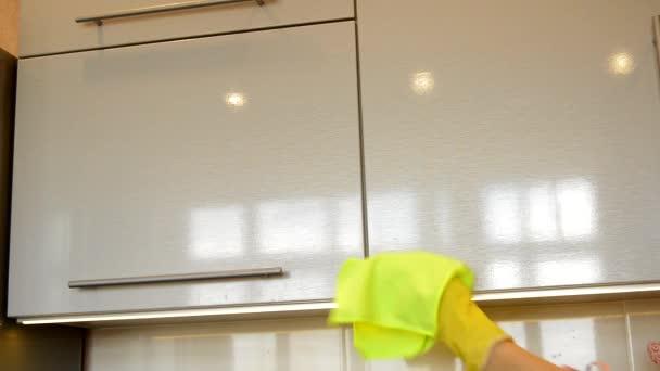 Ženská ruka ve žluté gumové rukavici čistí lesklý povrch moderní plastové kuchyňské skříňky látkou. Koncept jarního úklidu a domácí práce