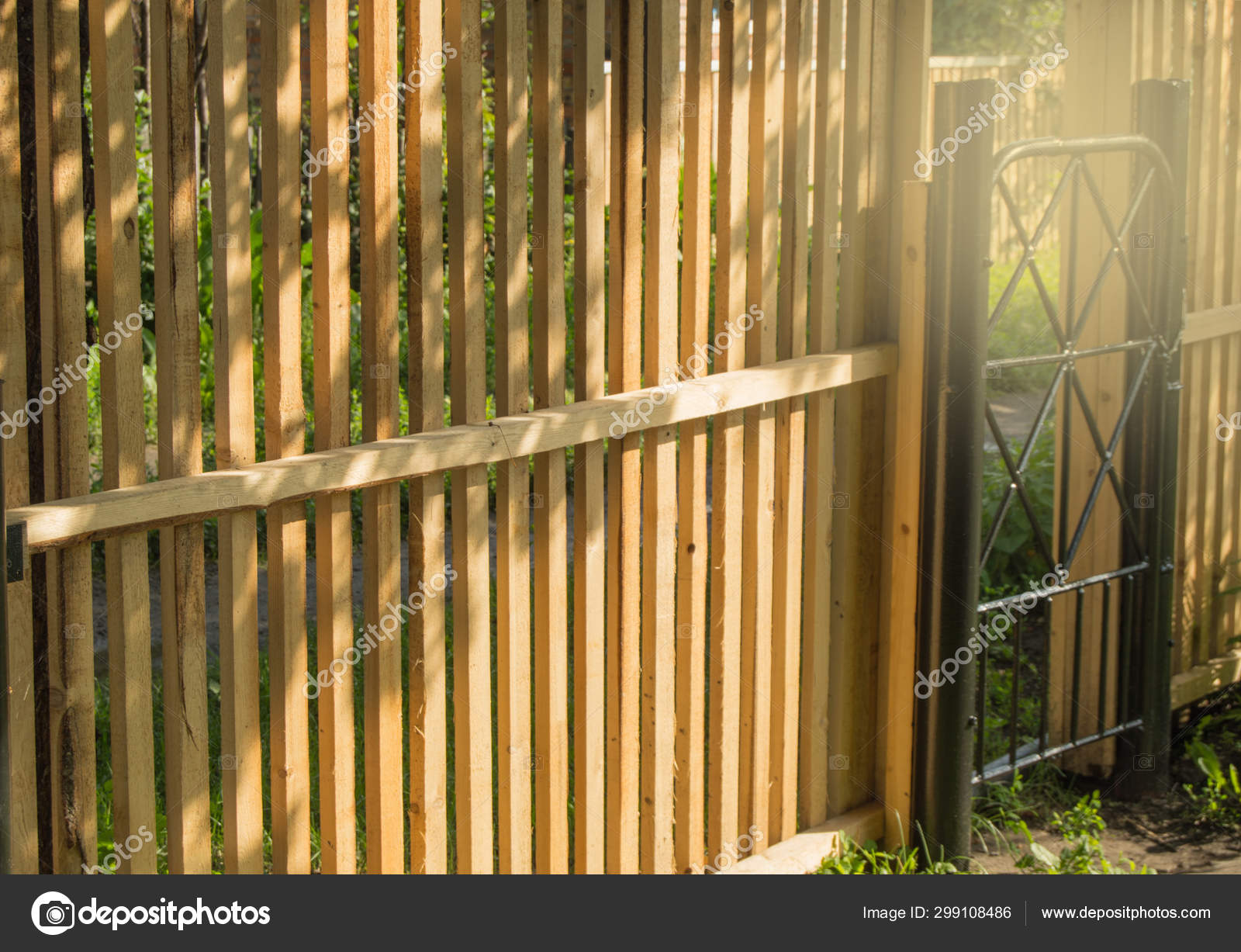 Picture of: Rustic New Wooden Fence With Black Metal Posts And Gates Garden And Vegetable Garden Fence On A Sunny Summer Day Against The Background Of Plants And Trees Stock Photo C Esweta3 Gmail Com