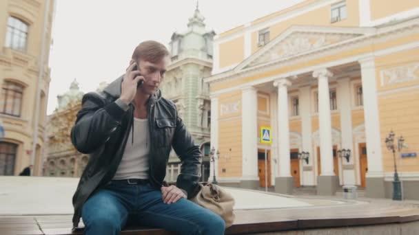 Brutální mladík mluví po telefonu v evropském městě