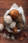 Užitečné fitness cukroví ze sušeného ovoce, ořechů a semen, bez cukru v skořápka kokosu na dřevěném prkénku hnědá. Vegetarián, vegan koncepce