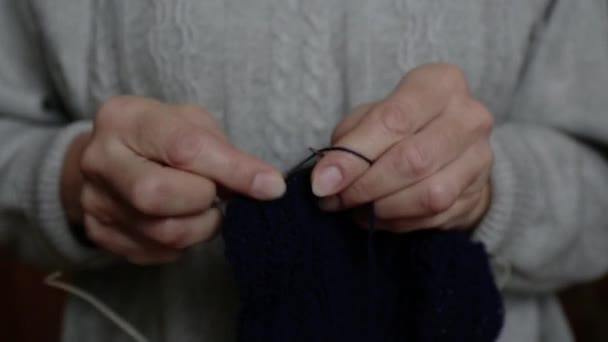 Knitting old woman. Close up hands of elderly woman. Macro soft focus.