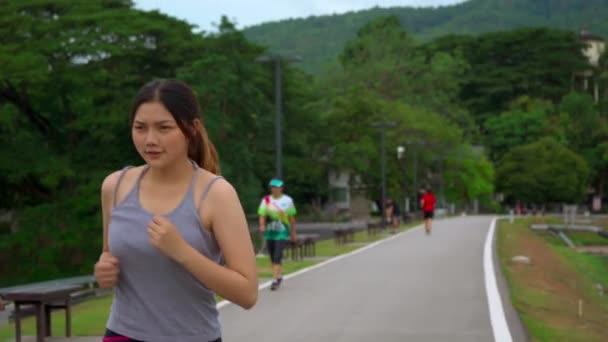 Krásná Asijská SPORTOVKA, která během ranní cvičení pobývá u jezera s výhledem na jezero a hory na pozadí, zdravý životní styl