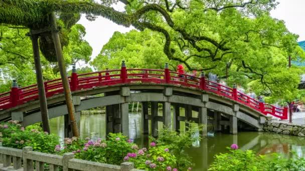 Dazaifu, Japonsko-10. července 2019-turisté a místní japonští lidé chodí přes překrásný červený most vedoucí ke slavné svatyni Tenmangu, která se nachází 10. července 2019 v Dazaifu v Japonsku