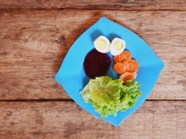 Blue square plate with beetroot carrots lettuce and eggs.