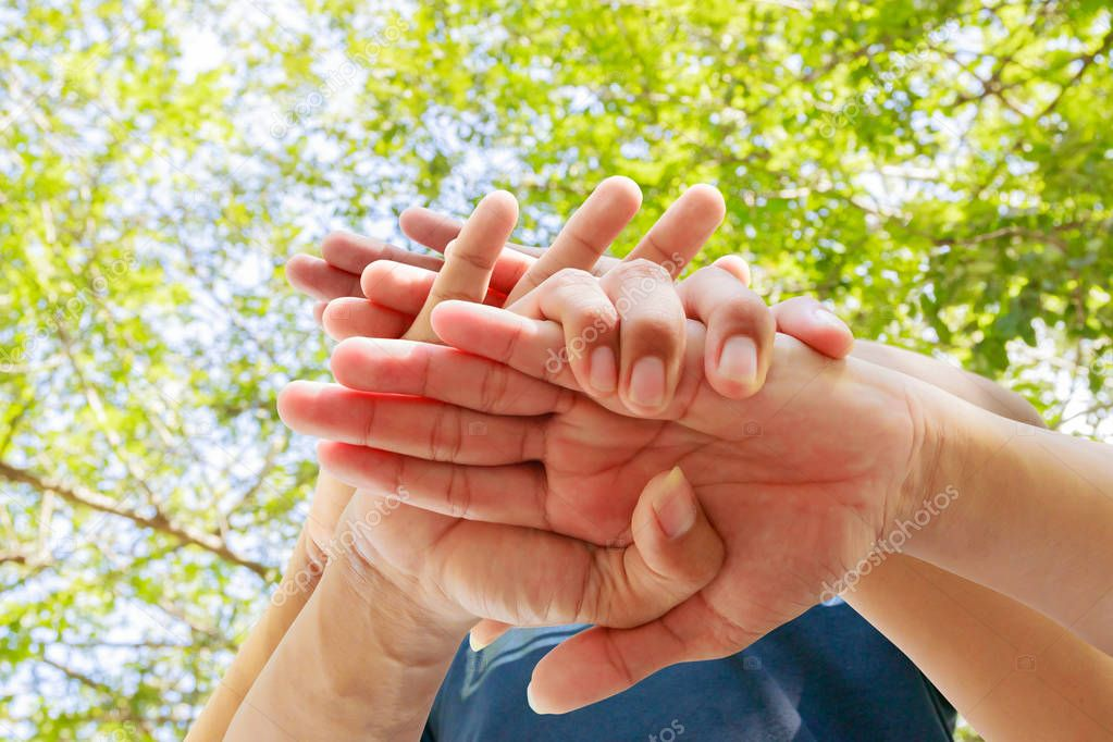 young people joining hands together in nature background