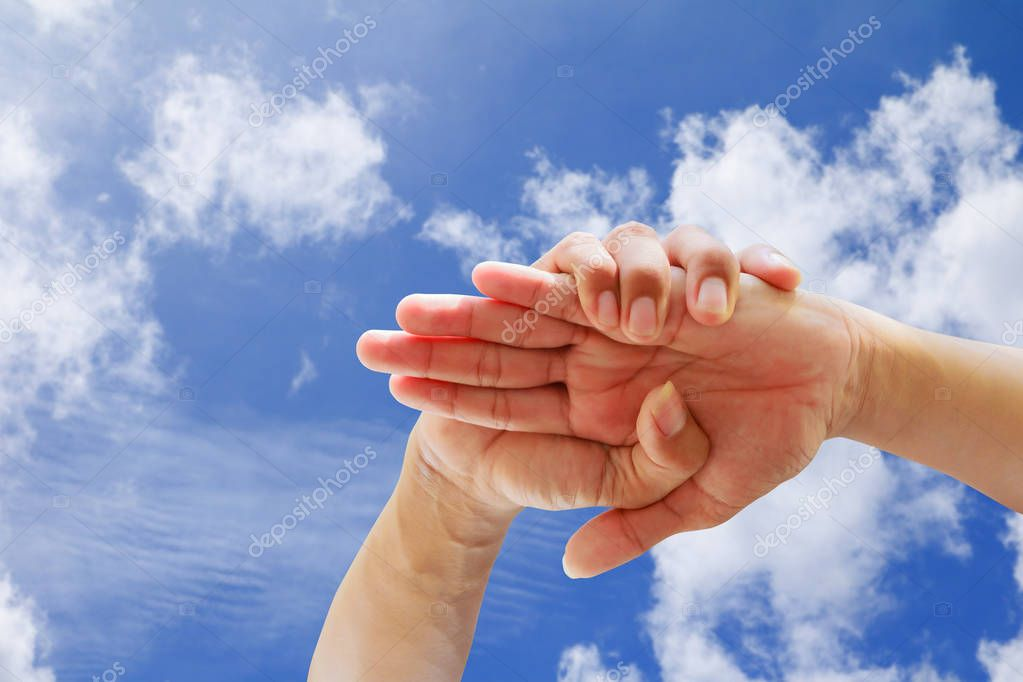 young people joining hands together in blue sky background