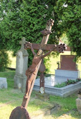 old tilted rusted cross with Jesus on the cemetery