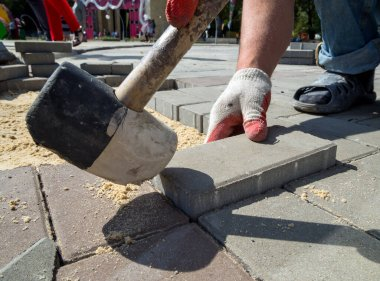 Worker puts paving stones with a mallet