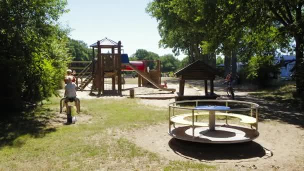 Děti hrát a bavit na hřišti s otáčením kolotoč během slunečného dne