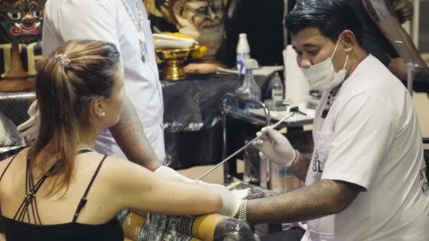Bangkok, Thailand: Commercial Sak Yant Master or Arjan is making a tattoo on customer in MBK Mall