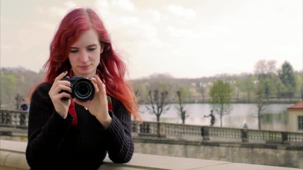 Cinemagraph - krásná dívka s červenými vlasy stojí u starověké místo nebo architektonických držte fotoaparát směrem k divákovi přidržujte prsty klikněte na obrázek