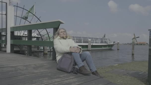 Old woman in white jacket is relaxing at ferry point with Dutch windmills in background (flat profile)