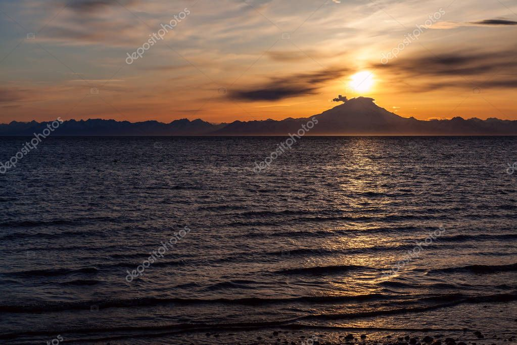The setting sun crests the summit of the active volcano, Mount Redoubt. Ninilchik, Alaska